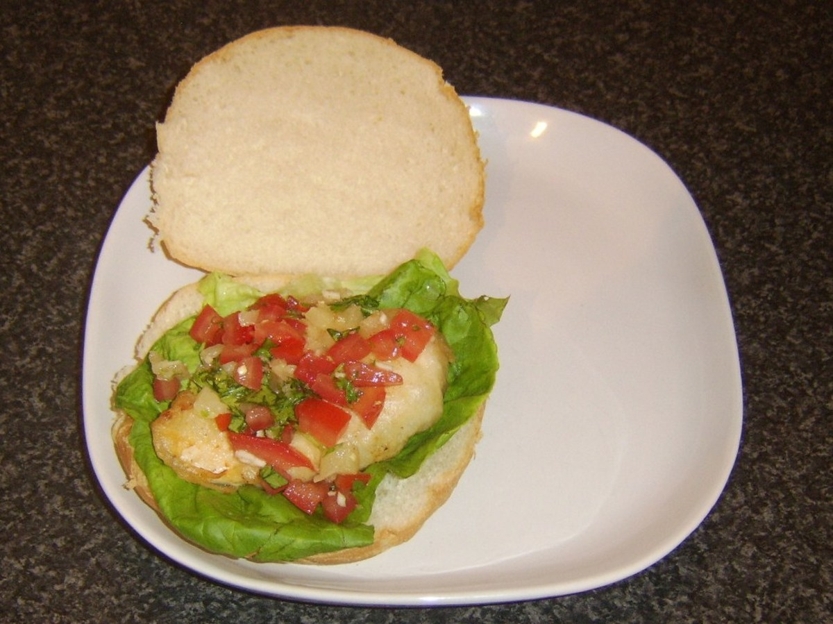 Pineapple salsa is spooned on to chicken burger