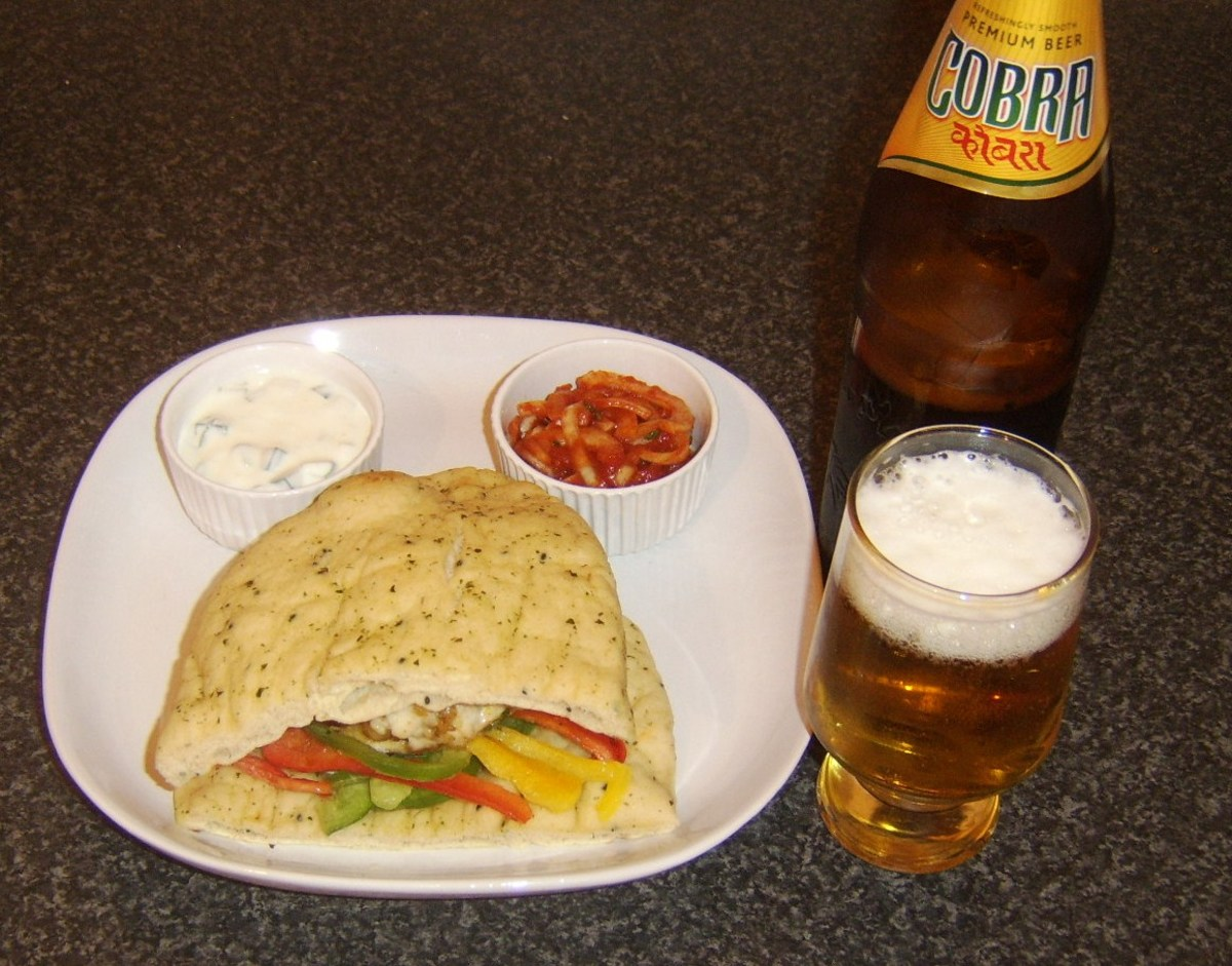 Curried chicken burger in naan bread is served with a glass of Indian beer