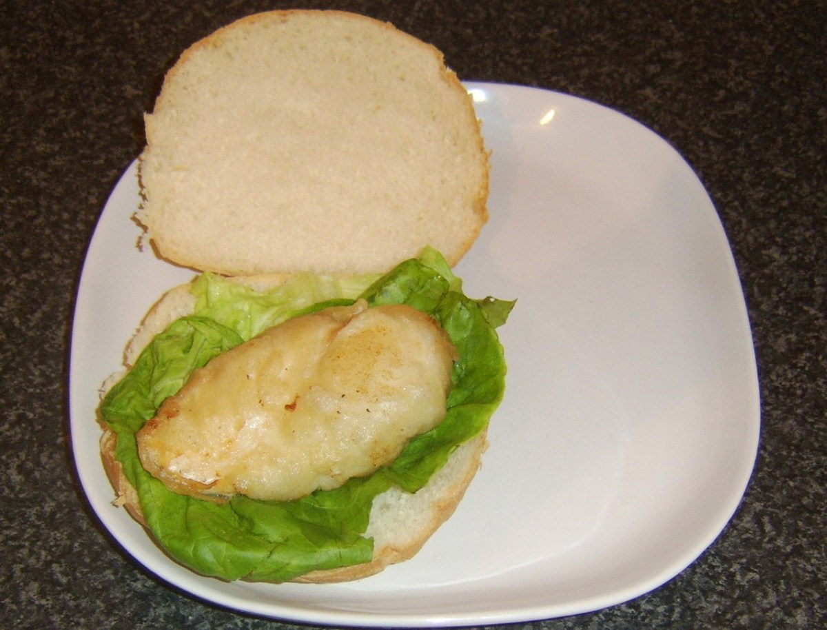 Chicken burger is laid on lettuce bed