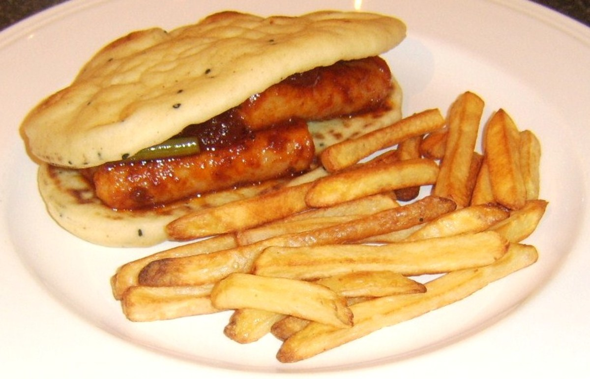 Sausages and green beans in a spicy szechuan tomato sauce naan bread sandwich with homemade chips