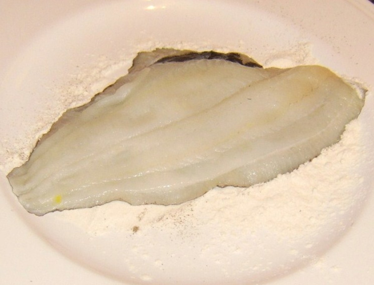 Skin side of plaice fillet is patted in seasoned flour