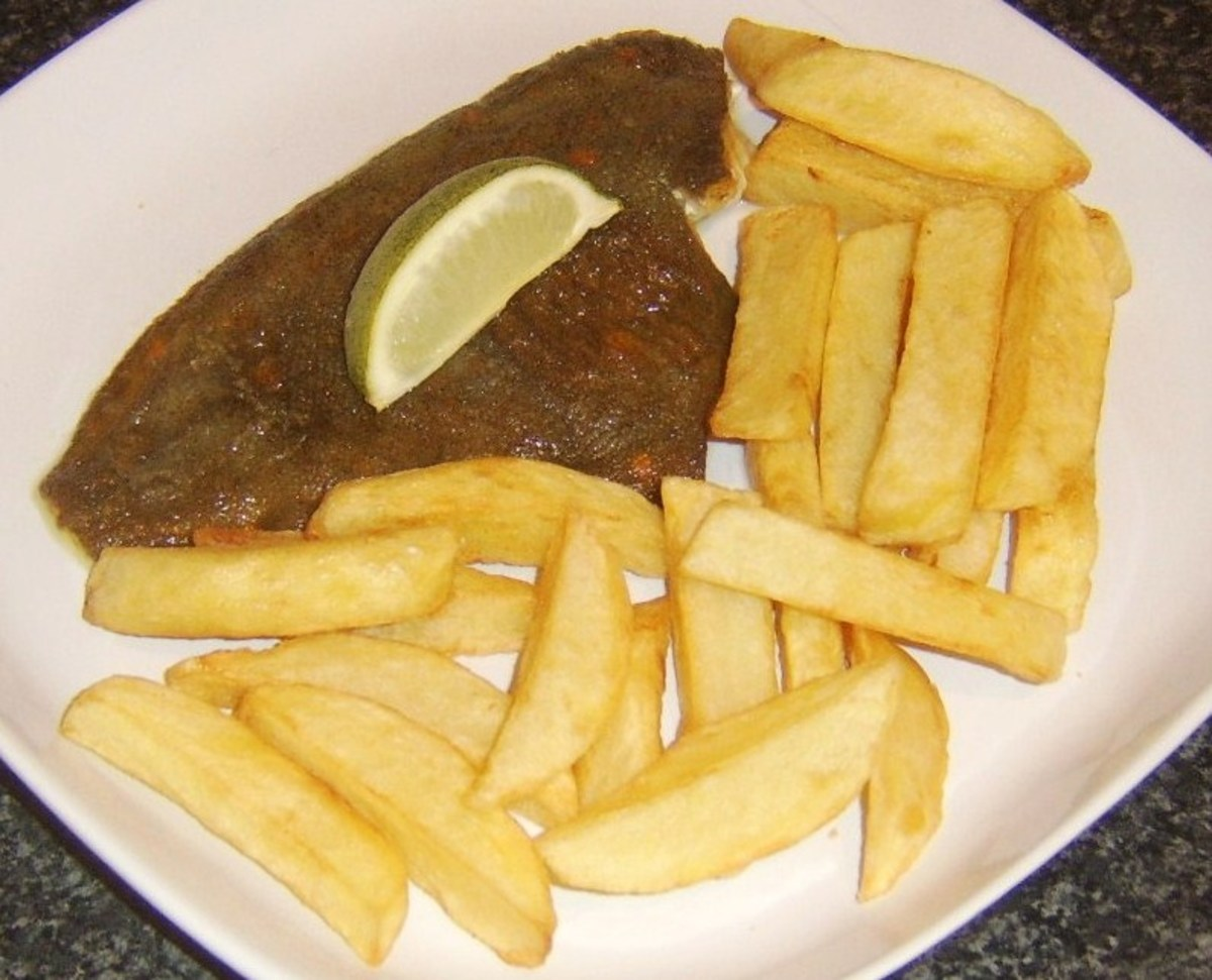 Skin on fried plaice fillet is served with homemade chips and a wedge of lime