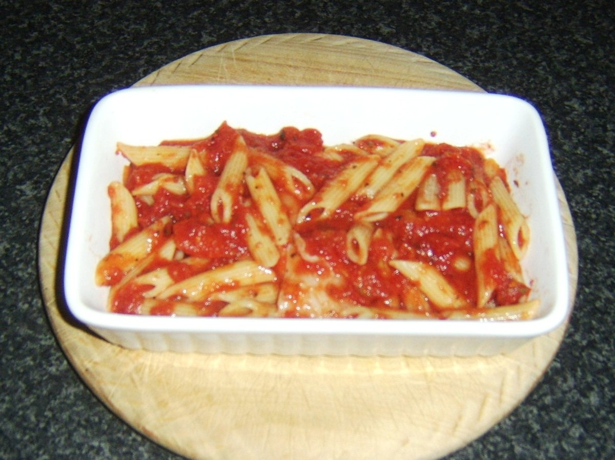 Plaice, pasta and tomato sauce are spooned in to ovenproof dish