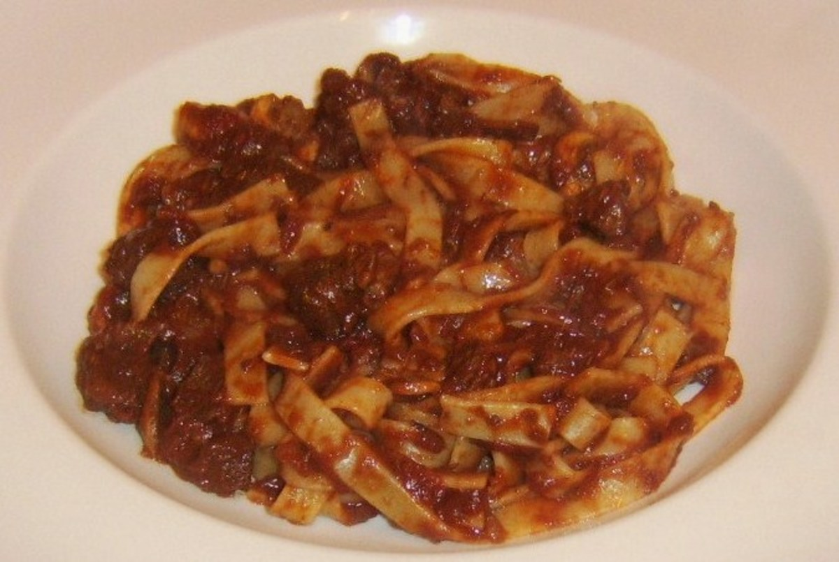 Tagliatelle in beef and red wine sauce is plated