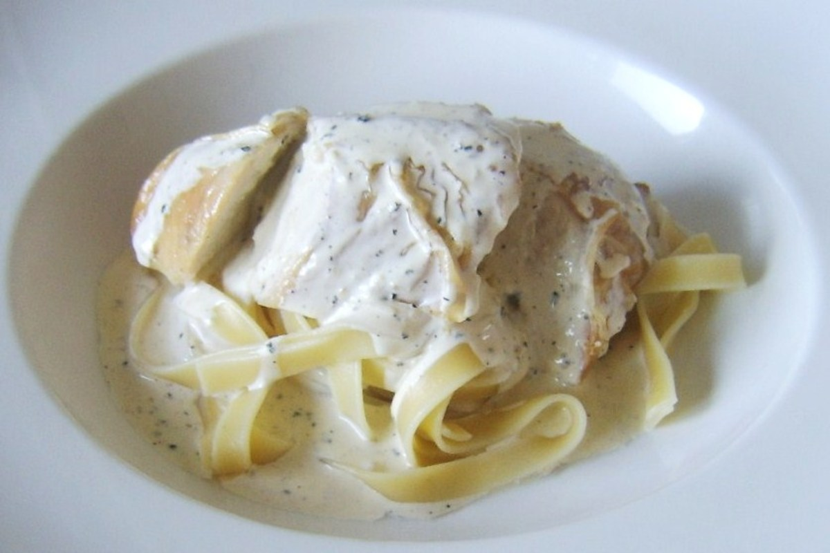 Sliced roast chicken breast is served on a bed of tagliatelle with a garlic and peppercorn cream sauce