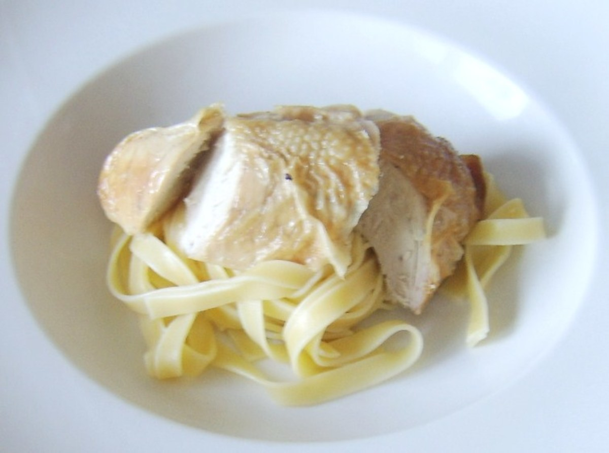 Sliced chicken breast is laid on tagliatelle bed