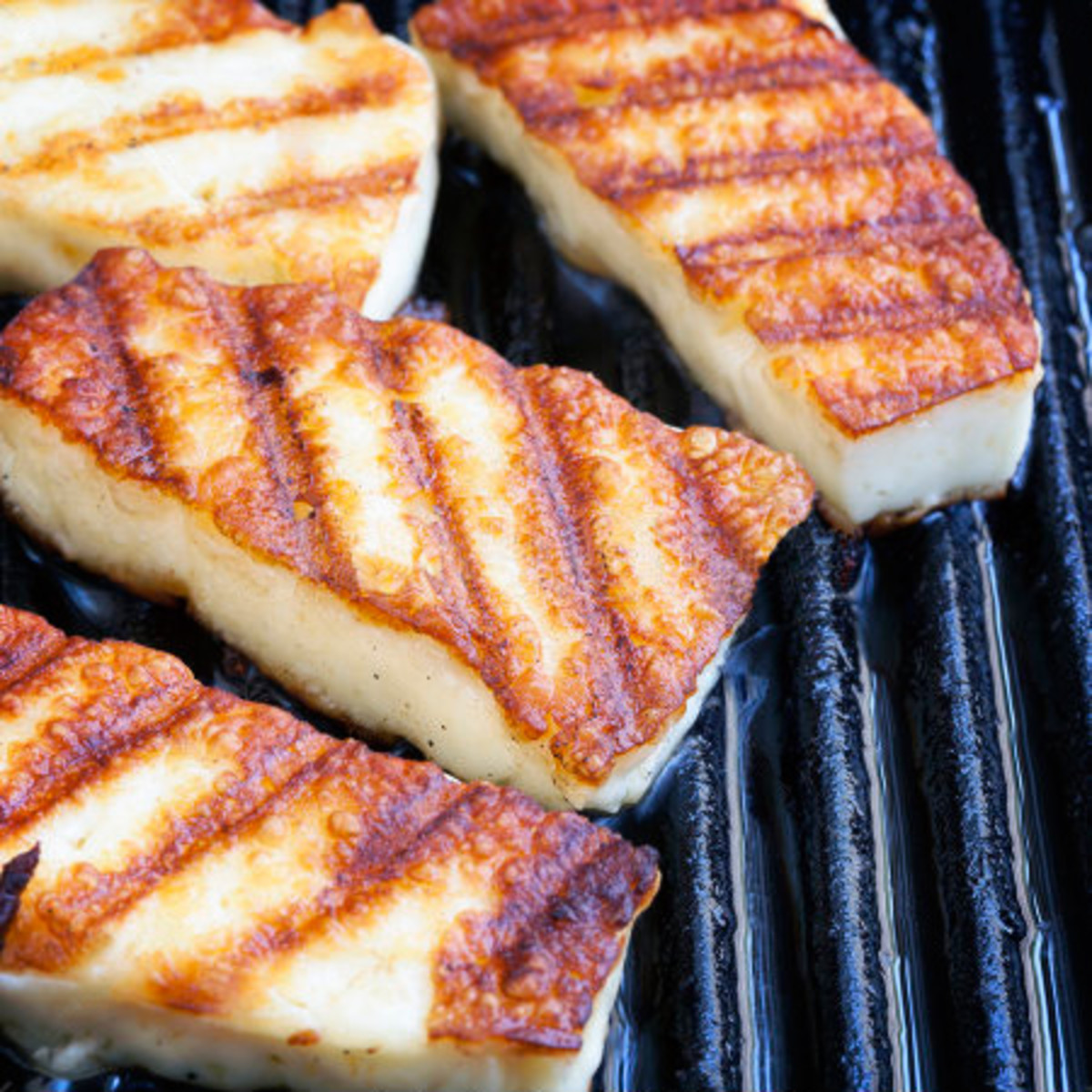 Searing halloumi cheese in a grill pan. Halloumi is a good choice for this type of frying, as it has a thicker texture, making it less likely to melt.