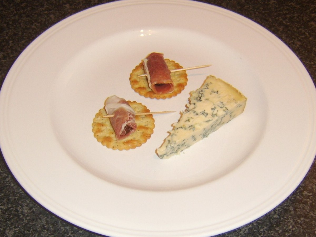 Stilton cheese with devils on horseback on crackers