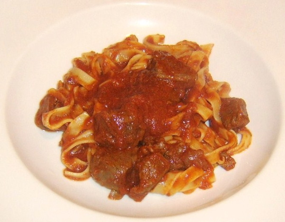 Tagliatelle with tomato and venison sauce is plated