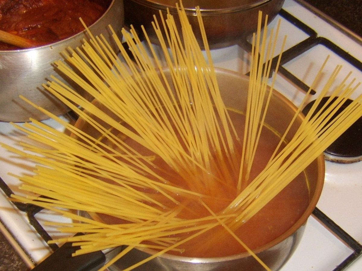 Spaghetti is added to turmeric spiced water