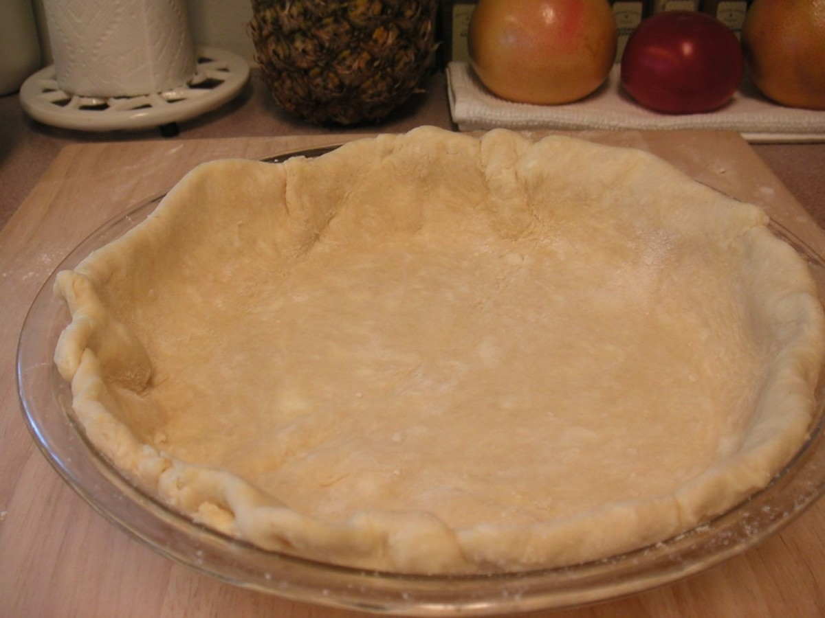 Using scissors or a knife, trim off the excess dough leaving about half an inch over the edges. Fold under the excess to form a rim along the outside.