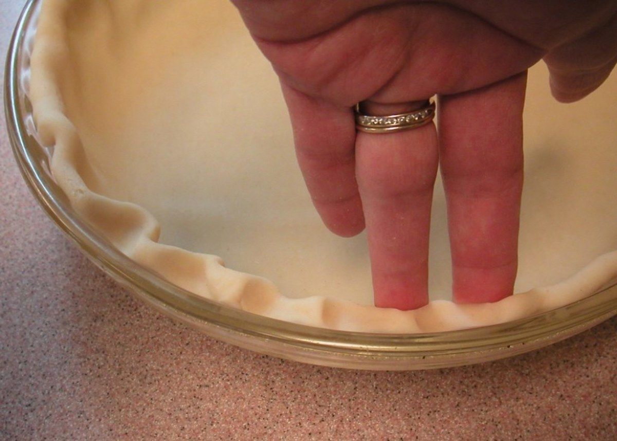 Use two fingers of one hand, pushing a finger from the other hand between them to form the fluted edge of the crust.