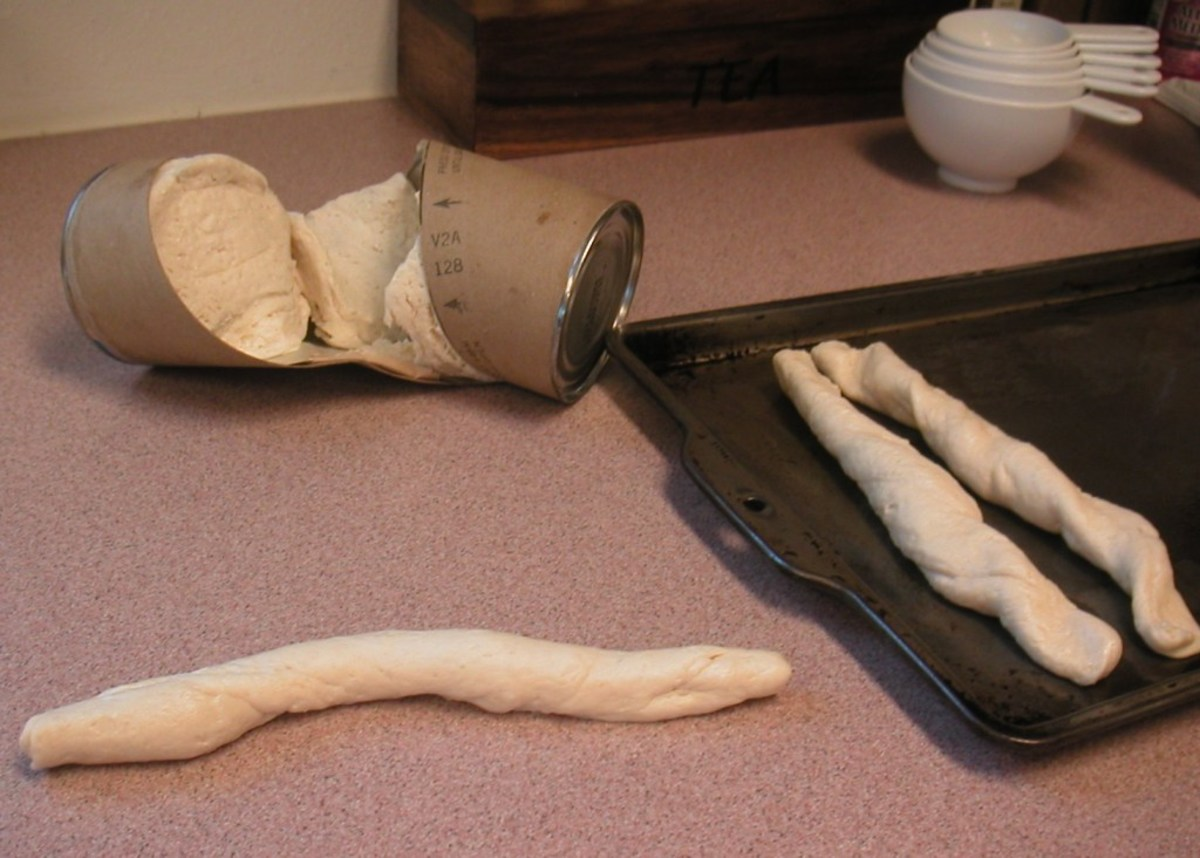 Separate the biscuits and roll between the palms to elongate. Press the ends down on the baking sheet to secure them.
