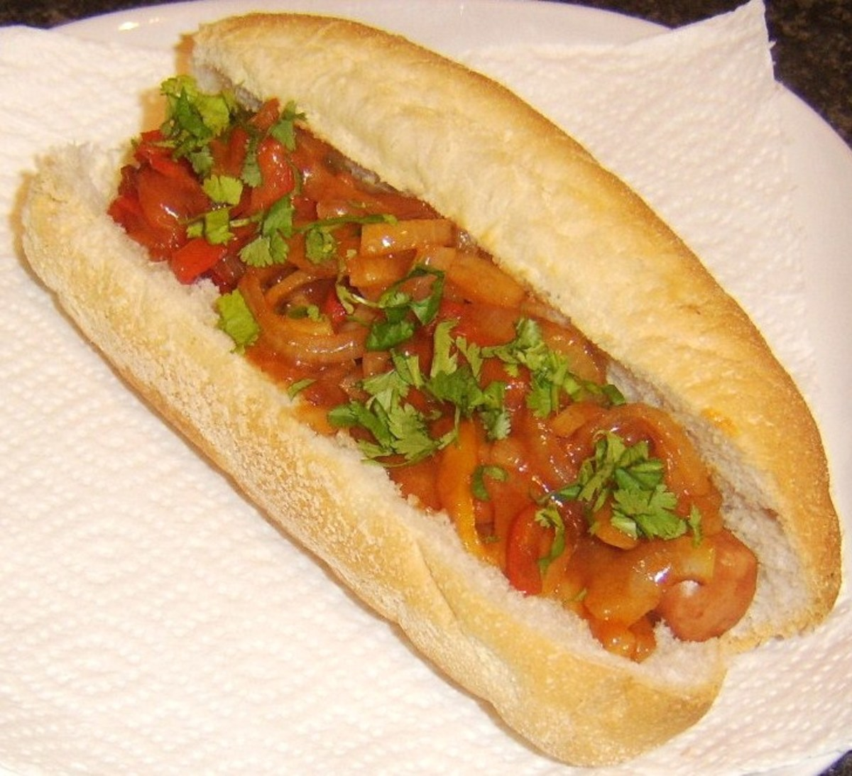 Bell peppers and onion in sweet and sour sauce topped dog