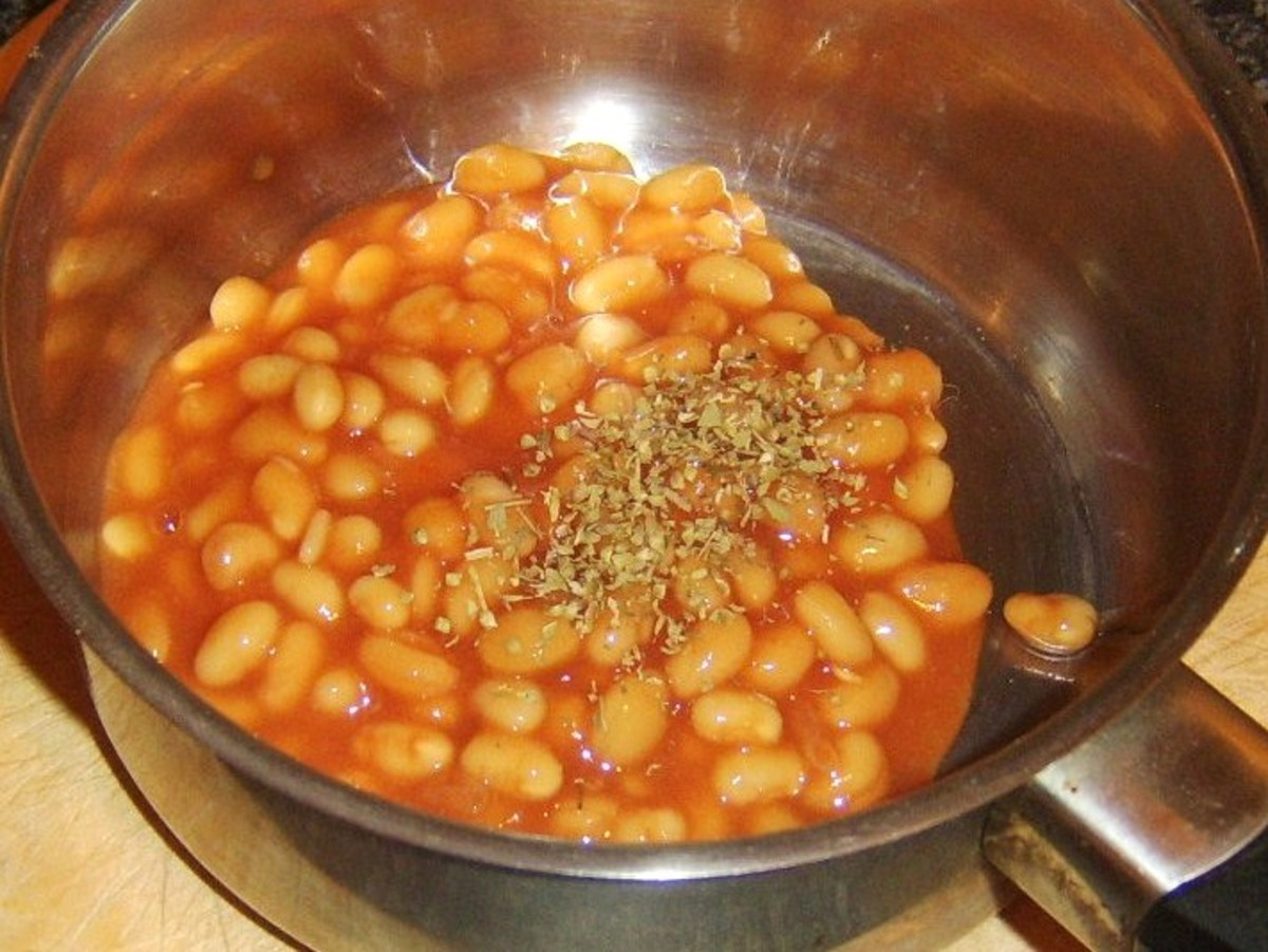 Dried oregano is added to baked beans in tomato sauce