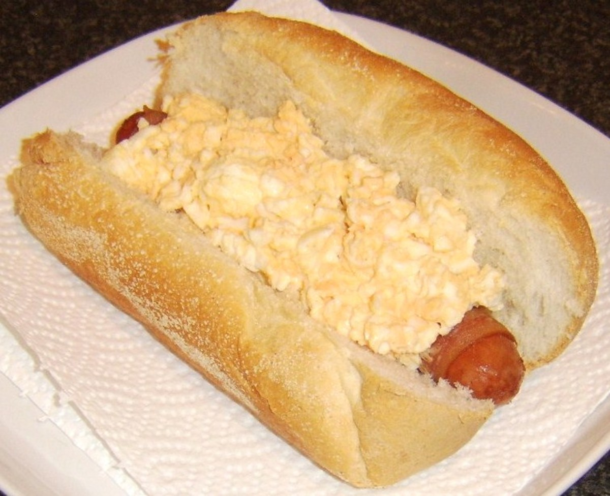 Egg mayo is spooned on to bacon dog