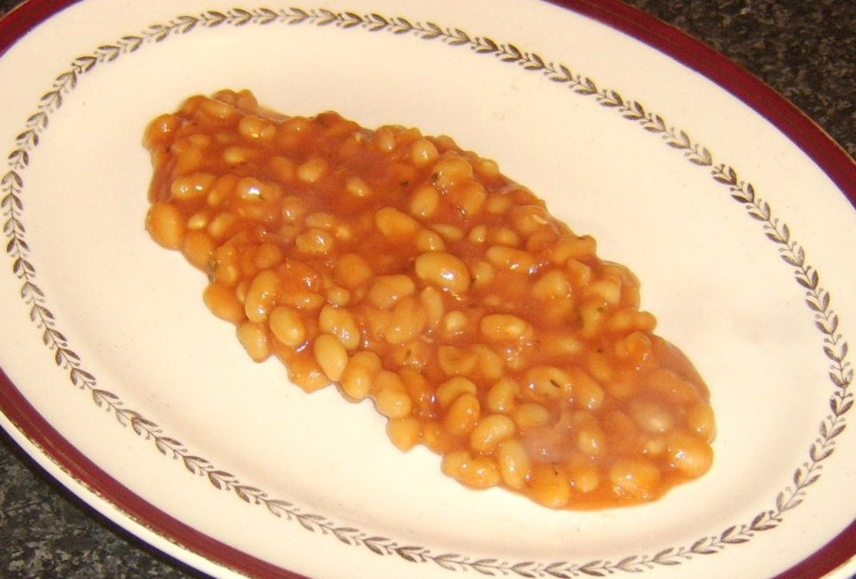 Baked beans are plated as a bed for sausage roll dog