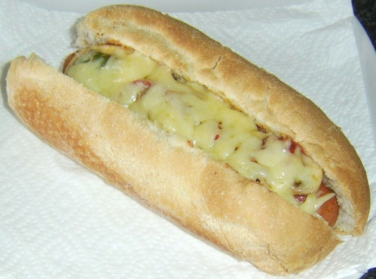 Hot dog topped with tomato sauce, stir fried mushrooms and peppers and melted cheddar cheese