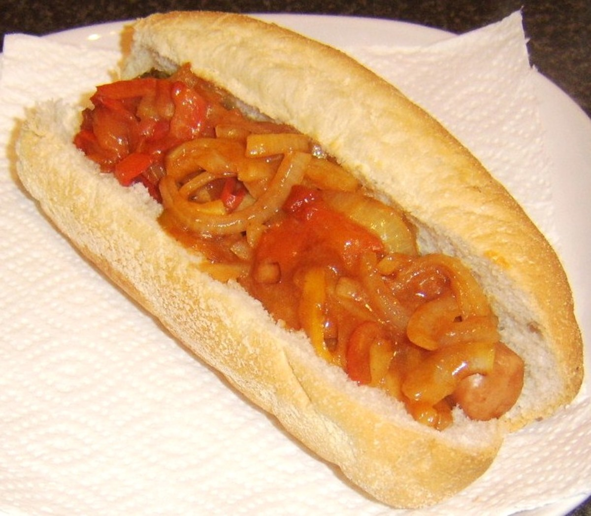 Sweet and sour peppers are spooned on to hot dog