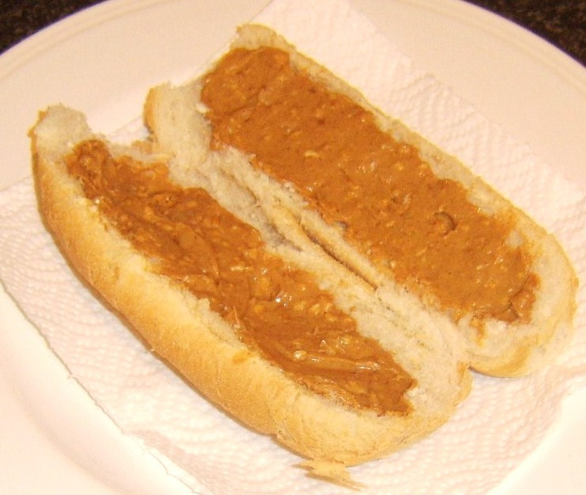 Peanut butter is spread on both sides of cut sub roll