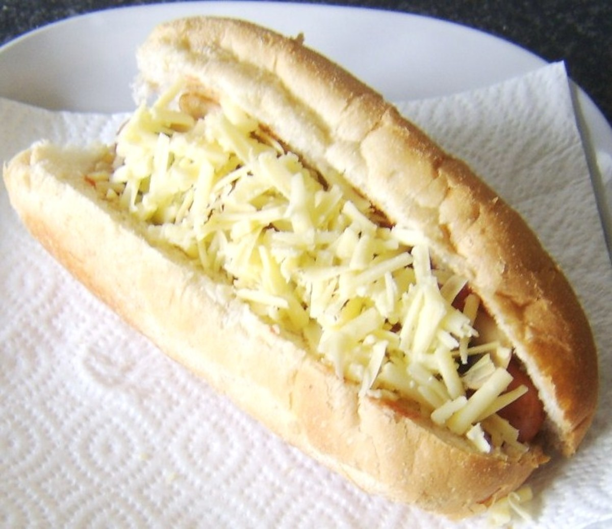 Grated cheese is scattered on hot dog for melting