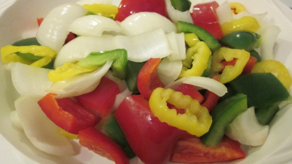 Red pepper, green pepper, sweet onion, and banana peppers cut in pieces for skewering.