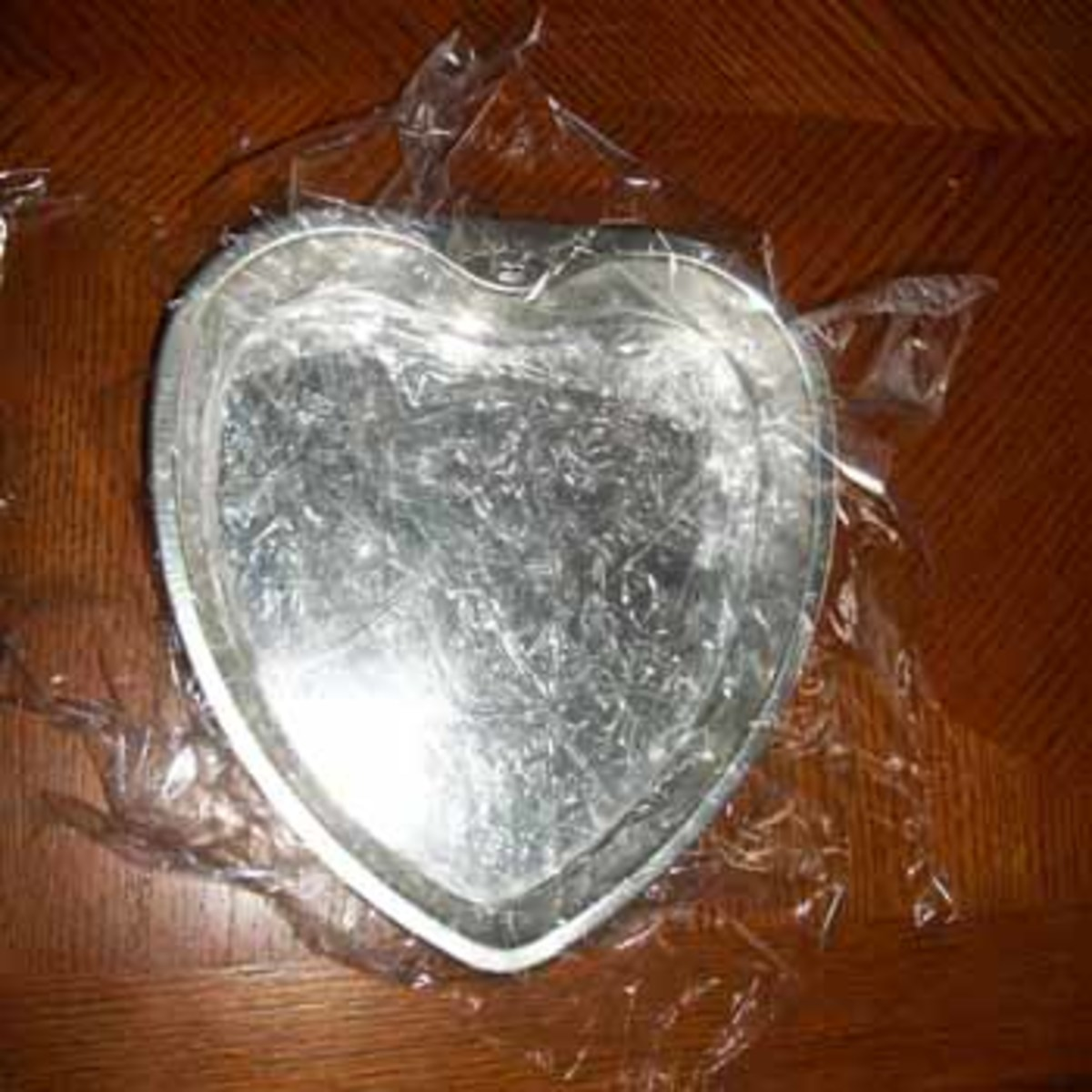 Heart-shaped pan lined with plastic wrap