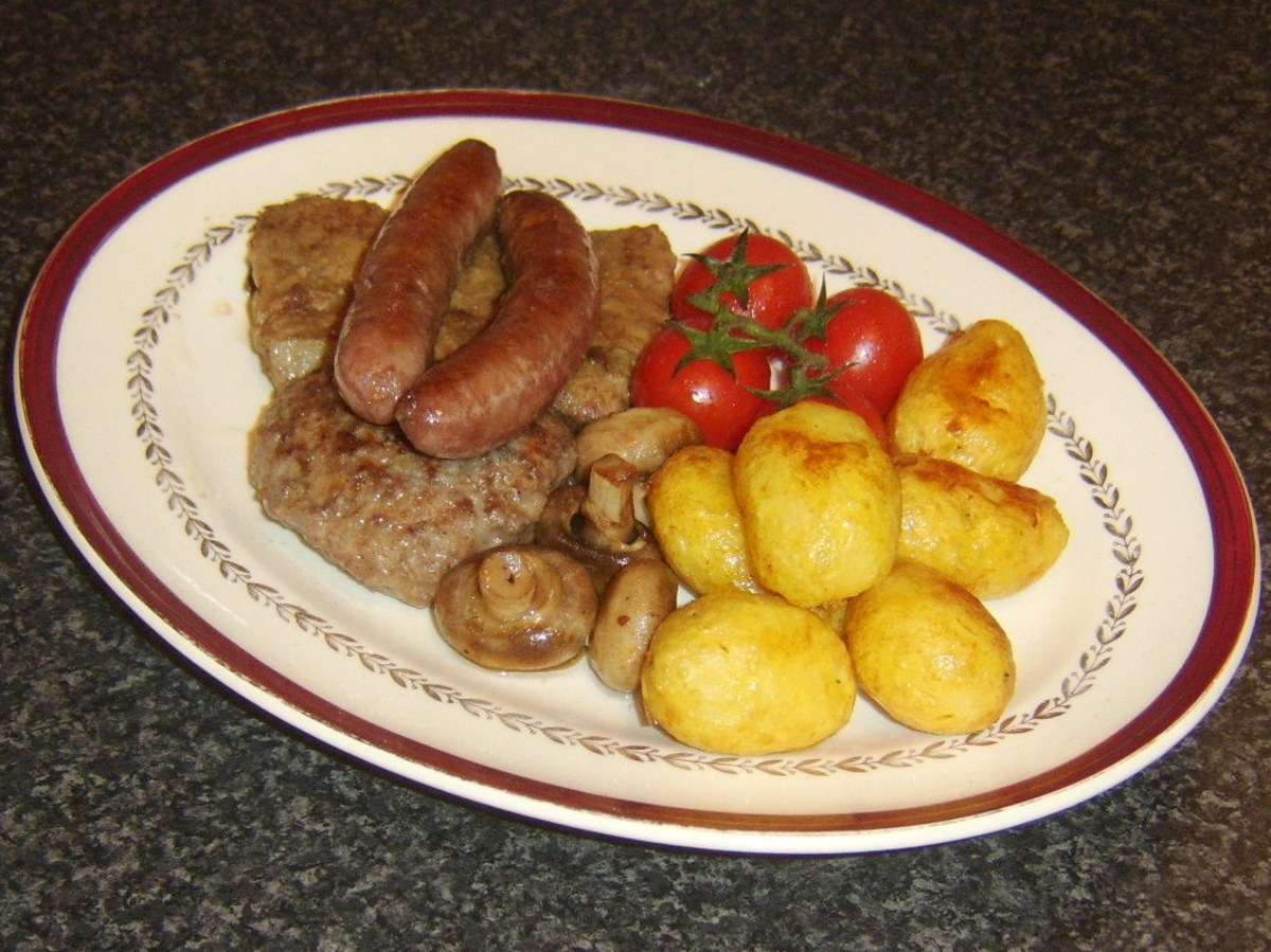 Fried ox liver with burger and sausages, potatoes, tomatoes and mushrooms