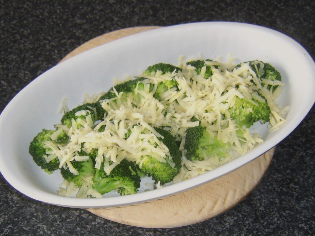 Cheese is grated over drained broccoli