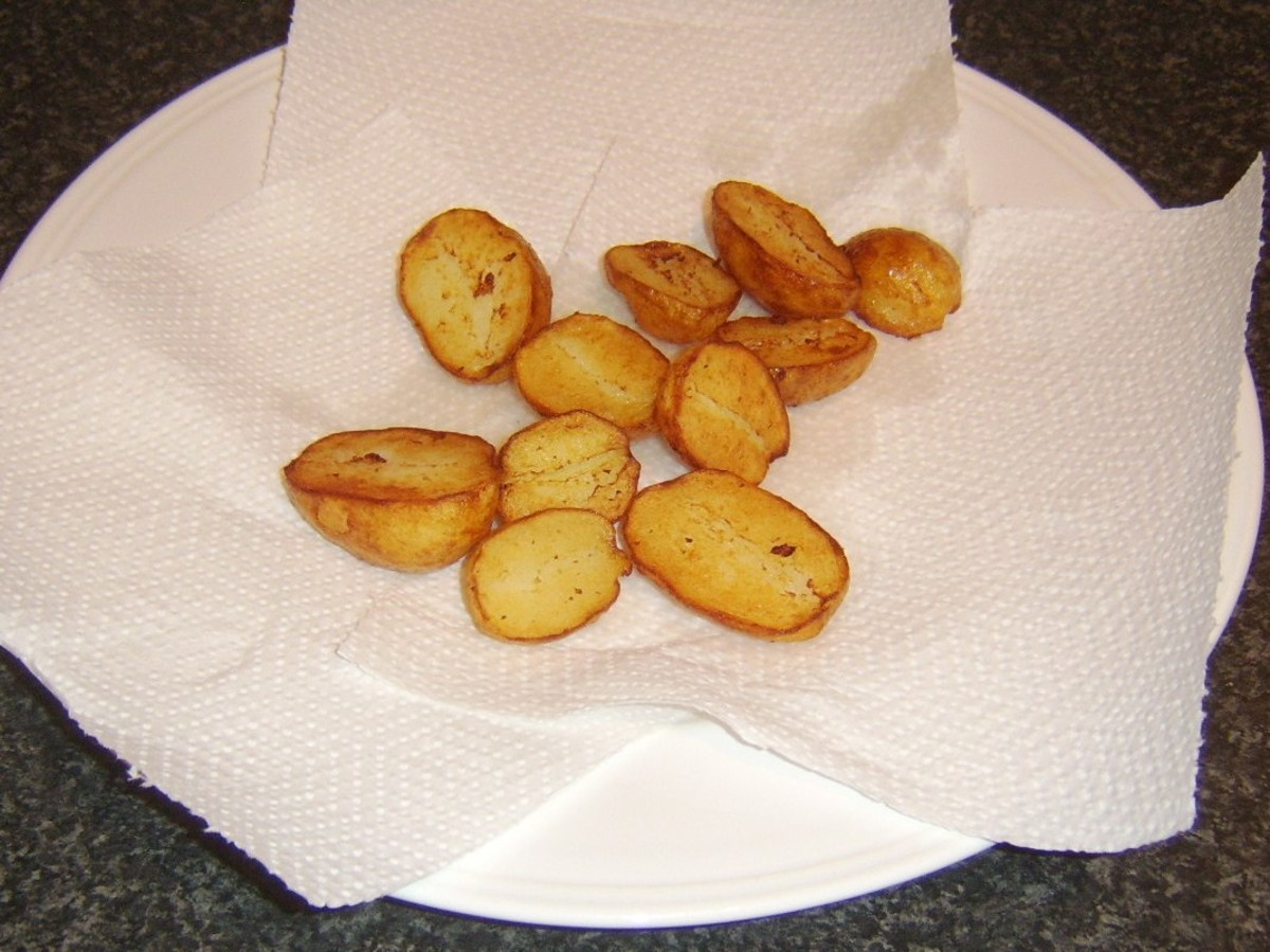 Pan roasted potatoes are drained on kitchen paper