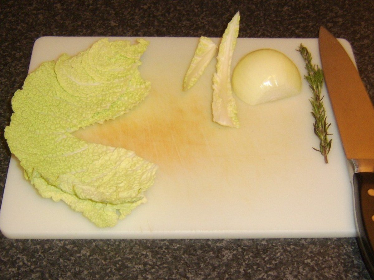 Tough central stalk is cut from Savoy cabbage leaves