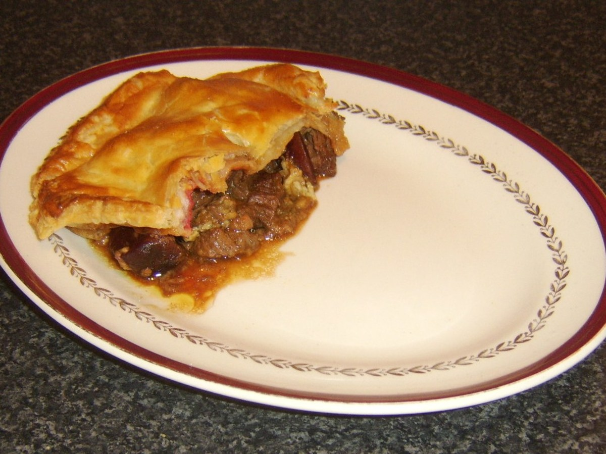 Pastry is plated on top of steak, beetroot and Stilton pie filling