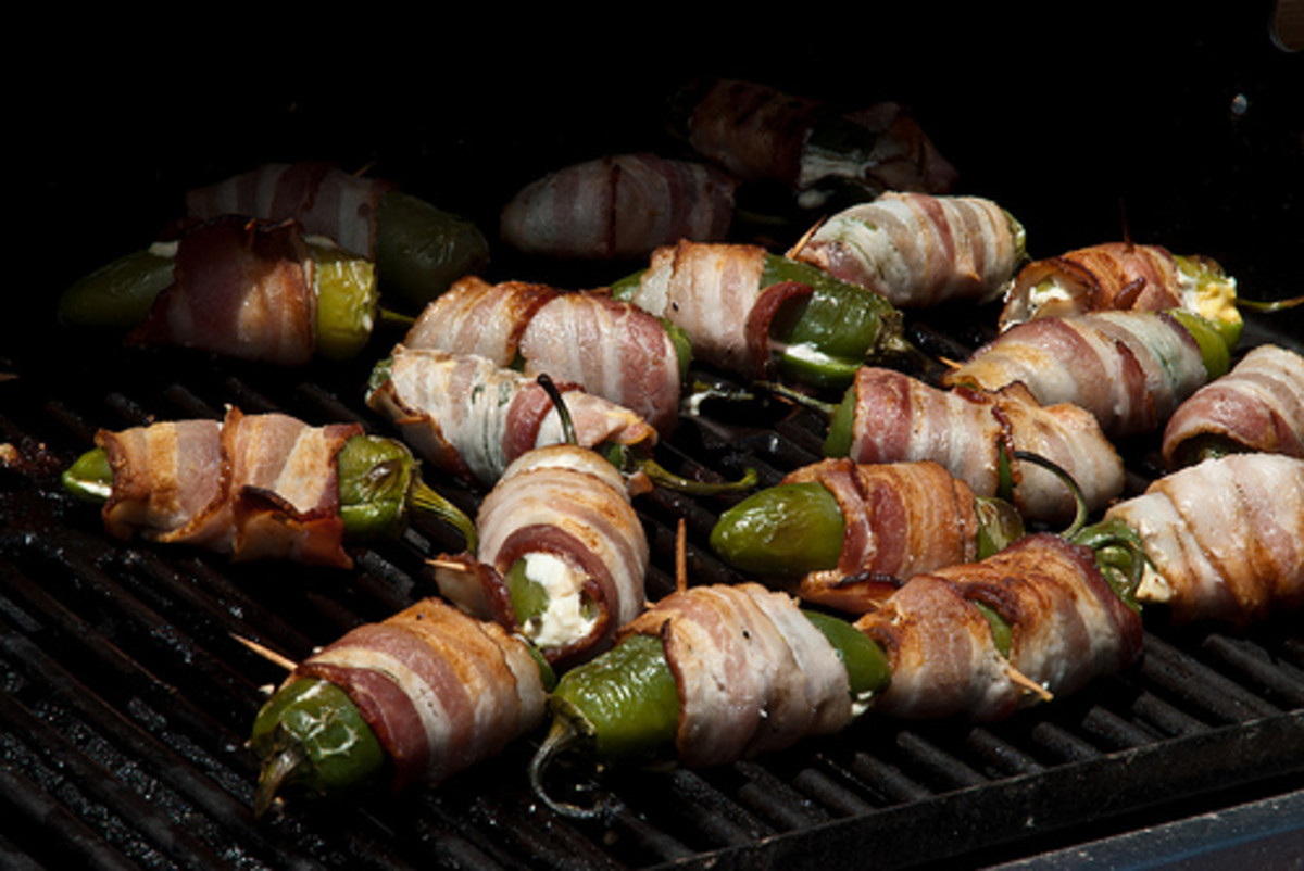 Jalapenos stuffed with cheese and wrapped in bacon on the grill