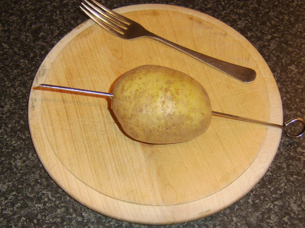 Potato is skewered for baking and pierced with fork