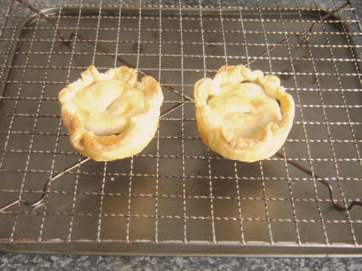 Christmas pudding pies are rested on wire rack