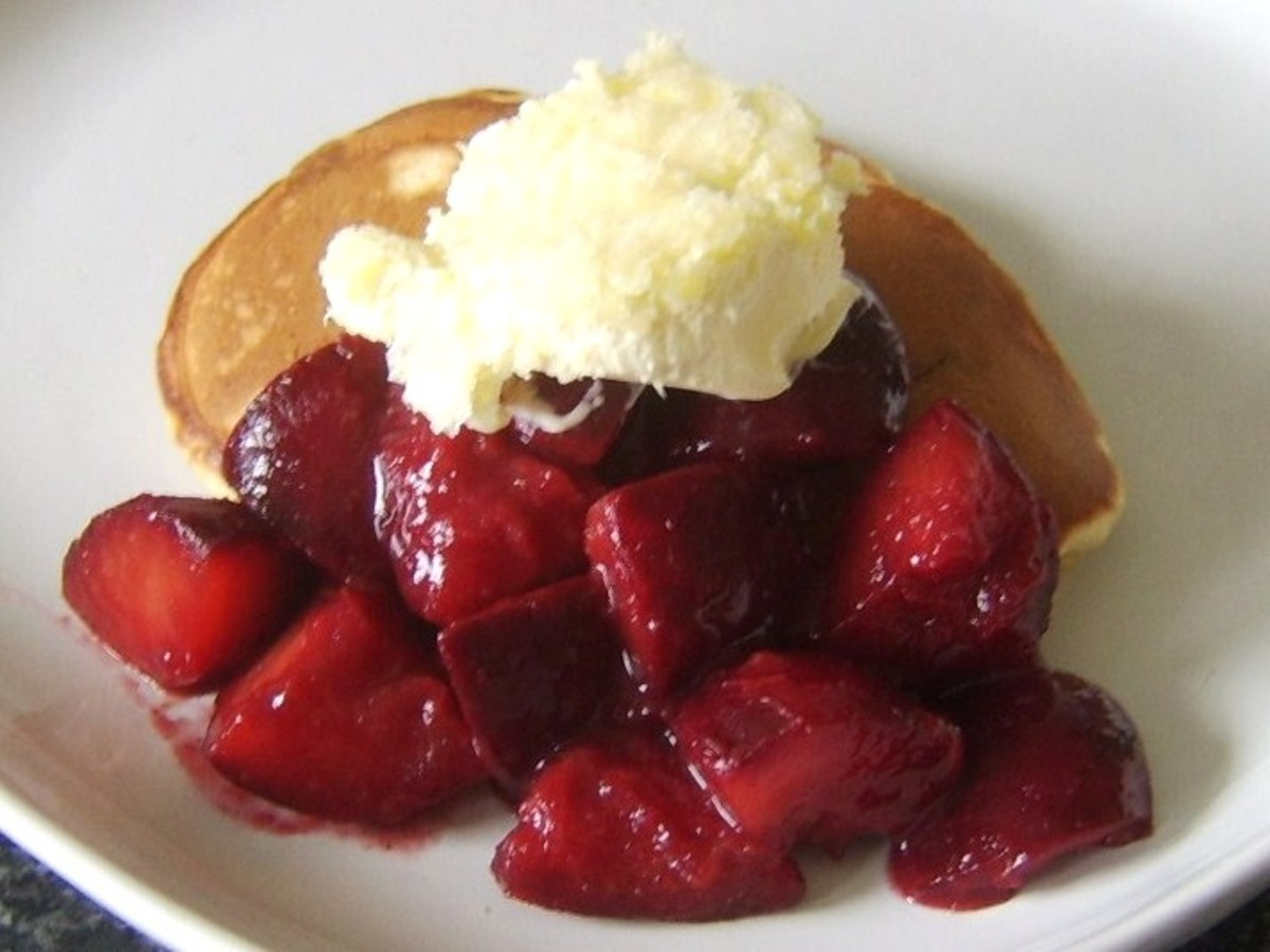 Stewed plums are spooned over Christmas pudding and topped with clotted cream