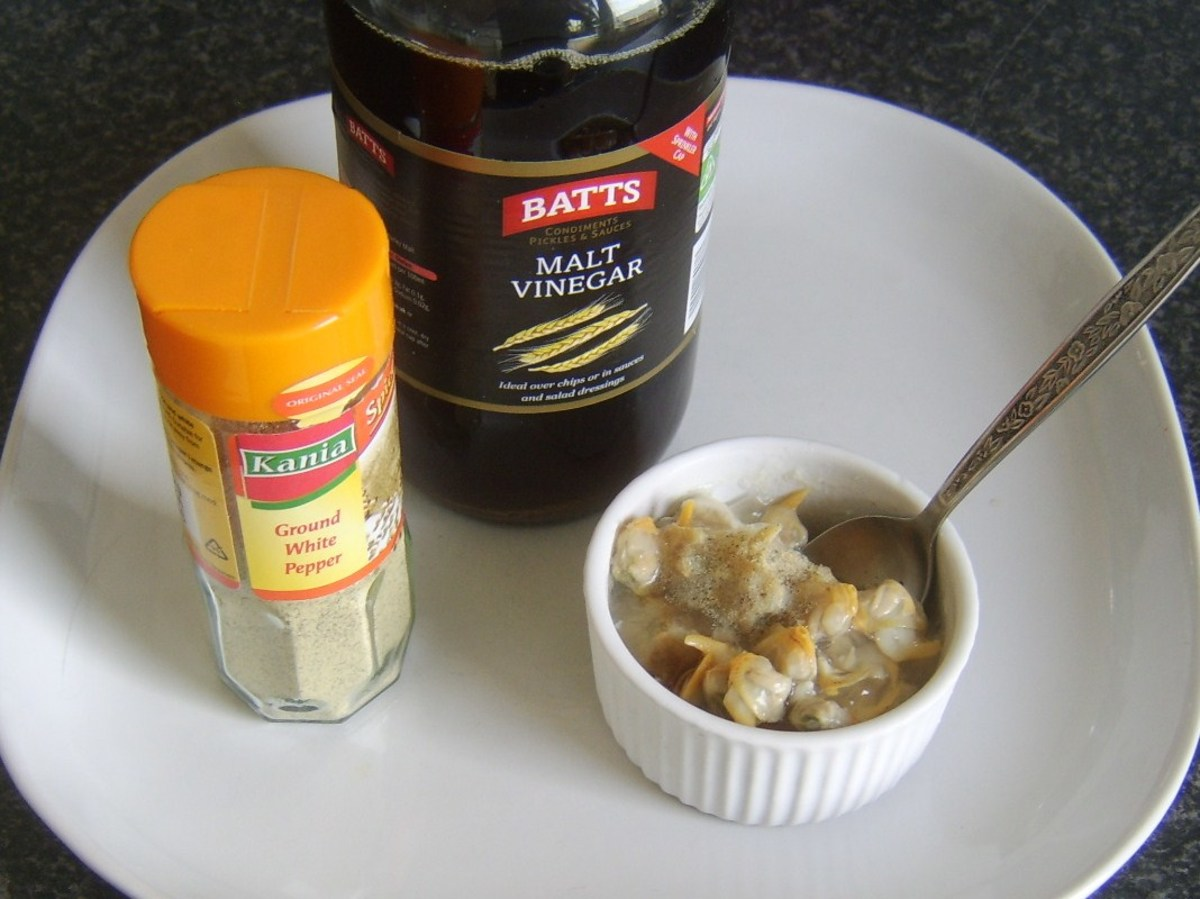 Seasoning jellied conger eel and cockles with malt vinegar and white pepper