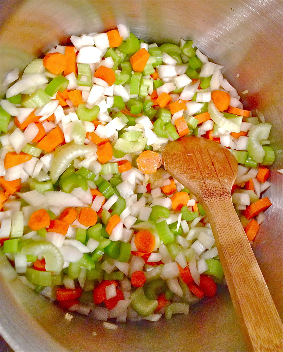 Heat oil over medium-low heat in large heavy soup pot, add onion, garlic, carrots and celery, cook until slightly tender and onions are translucent, about 10 minutes.