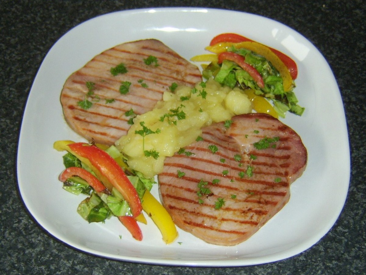 Griddled gammon steaks served with apple and pineapple sauce, sauteed cabbage and peppers.