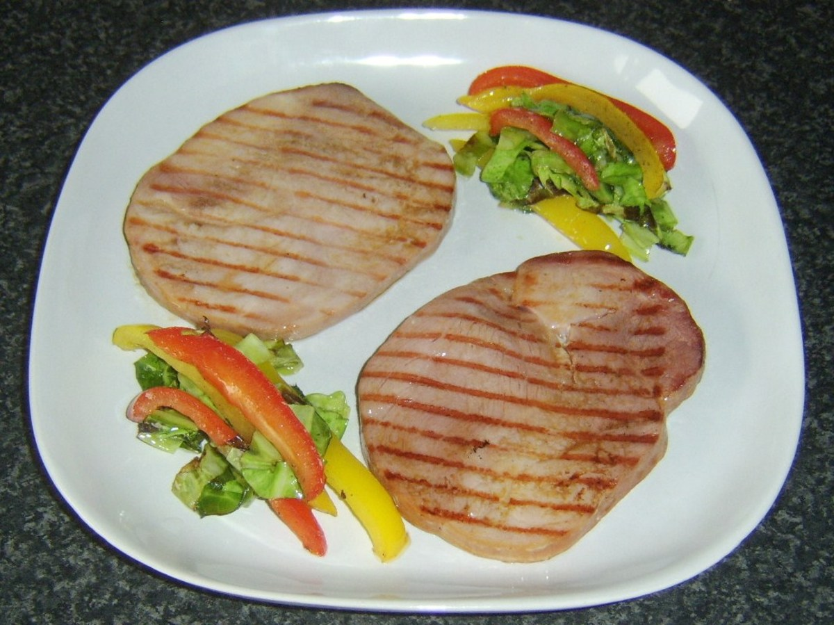 Sauteed cabbage and peppers are plated with gammon steaks