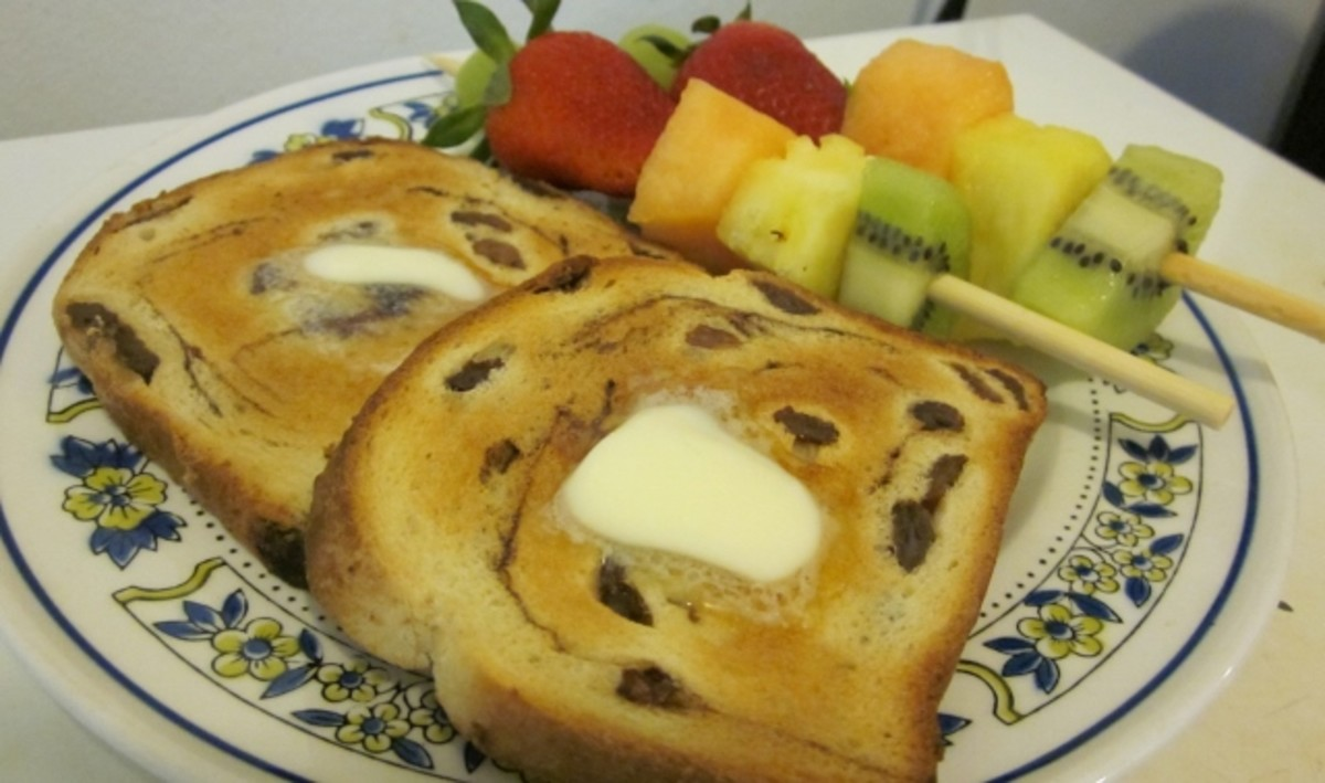 This serving suggestion for a light breakfast includes two fruit salad kabobs served with toasted raisin bread and butter.