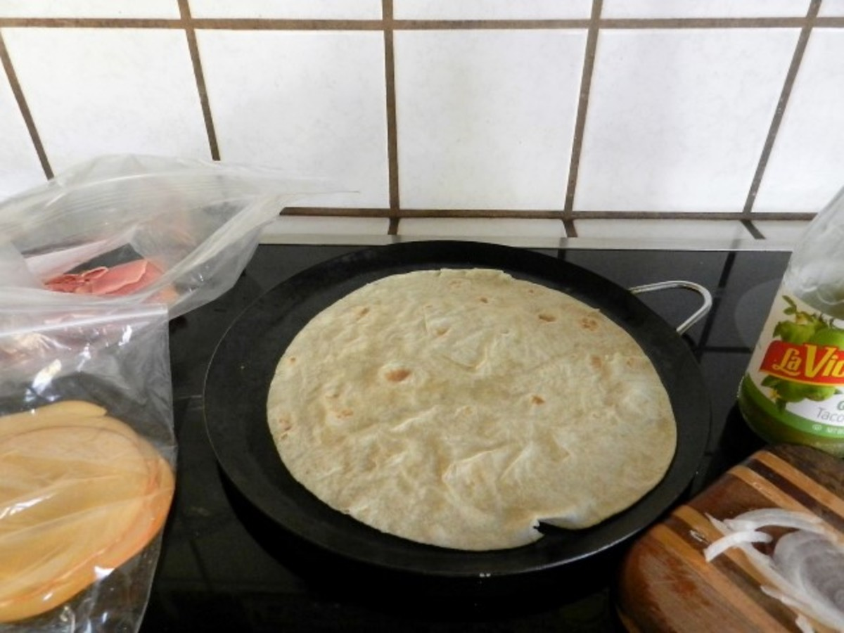 Heat the tortilla on a hot comal.