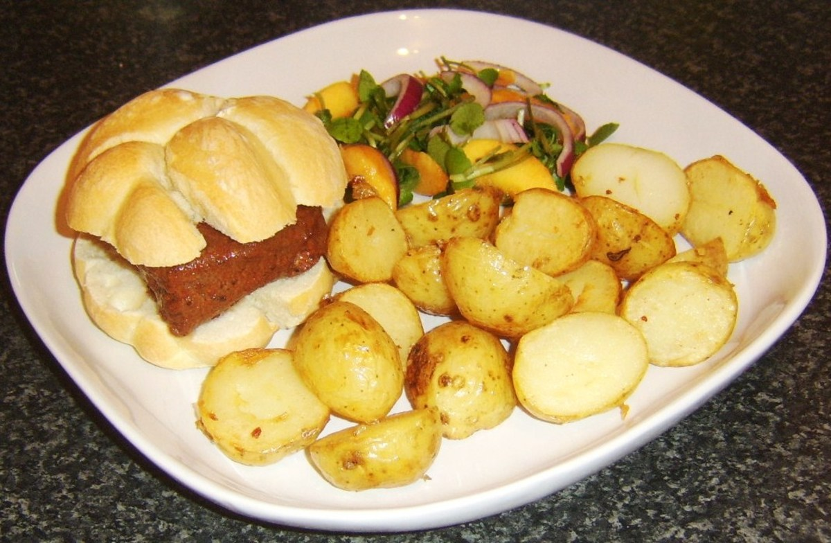Ostrich steak in marrakesh sauce is served on a bread roll with deep fried potato halves and a peach and watercress salad