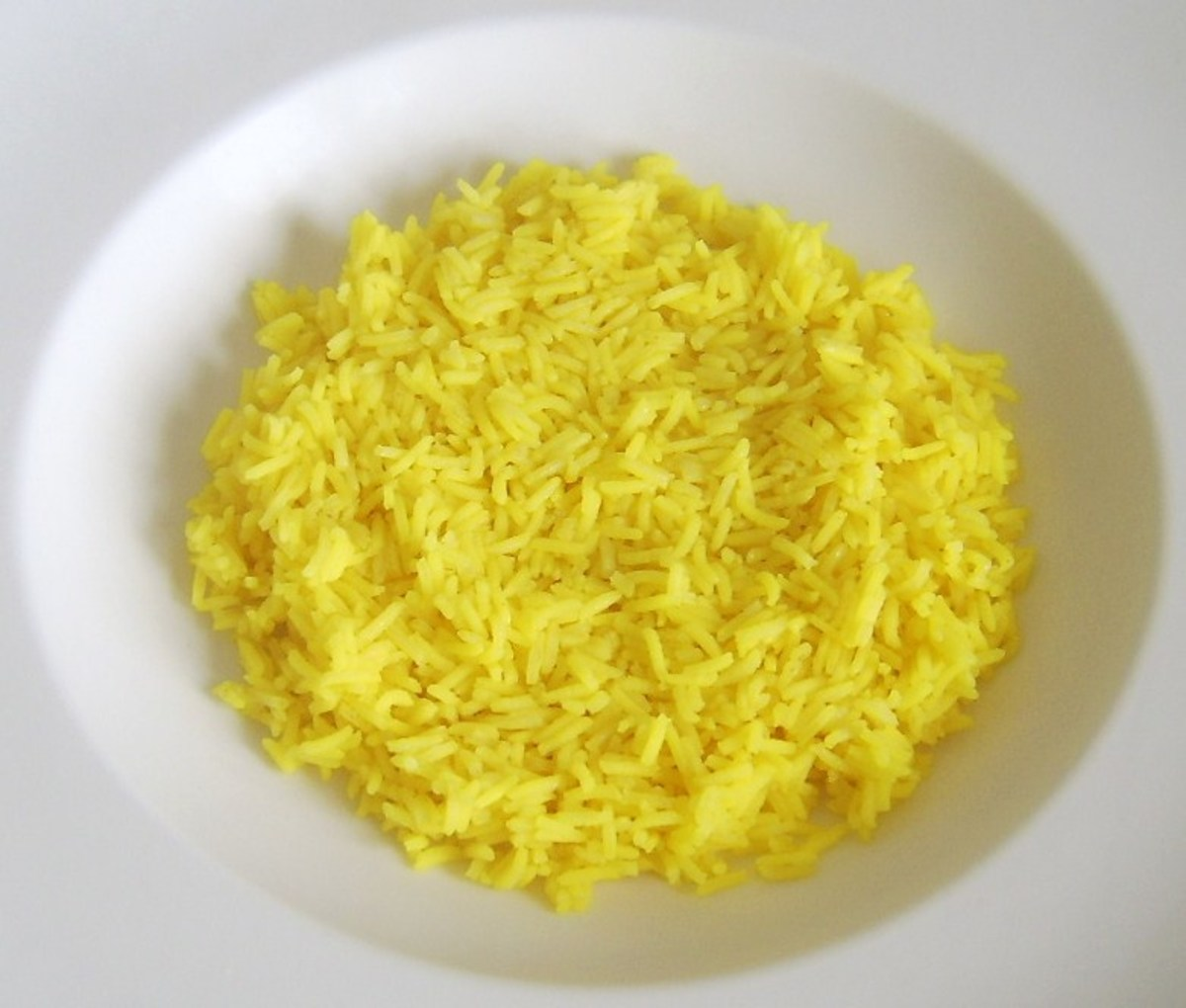 Bed of turmeric spiced rice in serving plate