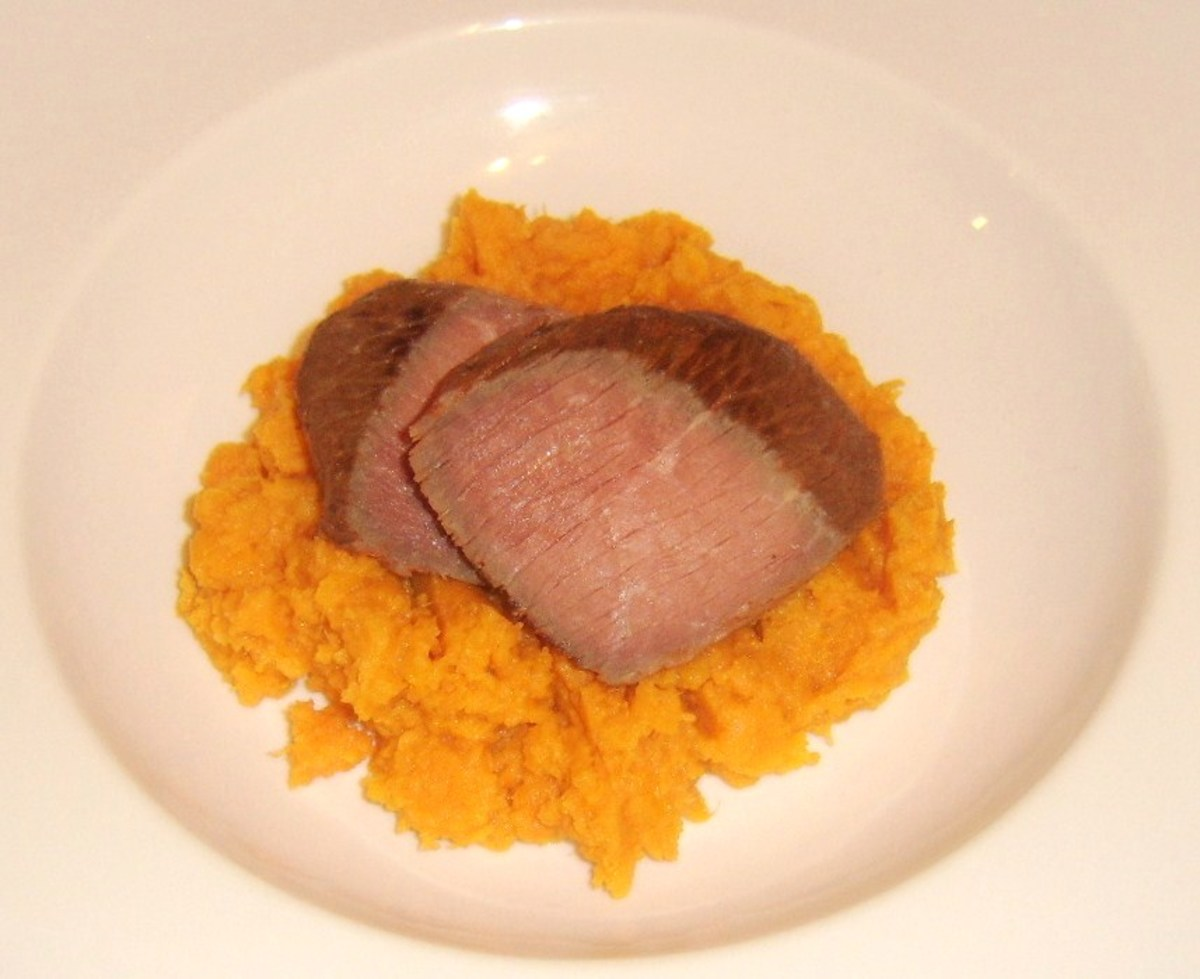 Ostrich steak halves are laid on sweet potato mash