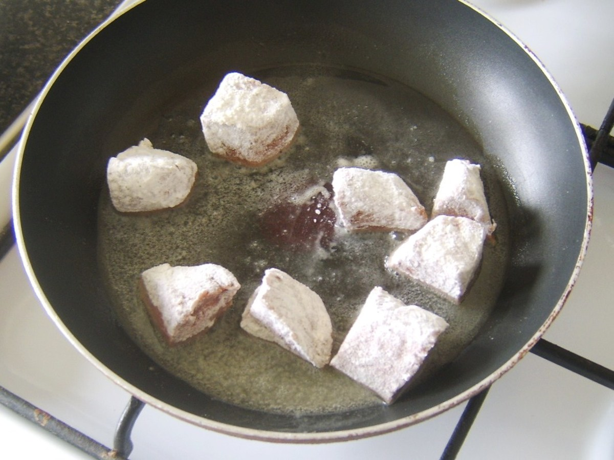 Floured ostrich steak pieces are added to frying pan