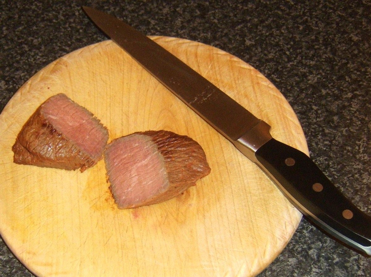 Rested ostrich steak is halved
