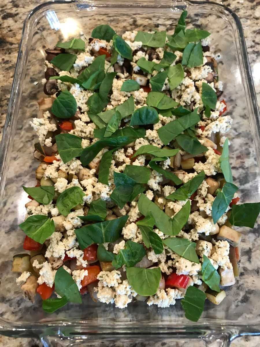 Spread half of tofu mixture, 1/4 cup of plant-based cheese (if using), and half of the sliced basil or baby spinach over roasted vegetables.