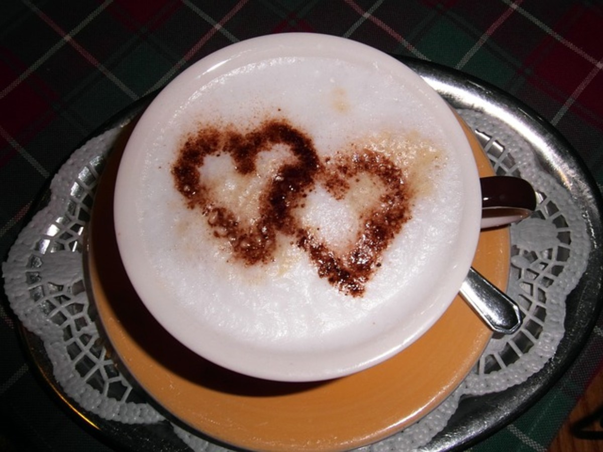 Cappucino coffee drink featuring two love hearts on the foam.  A creamy and thick head is essential for cappuccino drinks.  Creative people use the foam to make engaging images and patterns for coffee drinkers in cafes and restaurants.