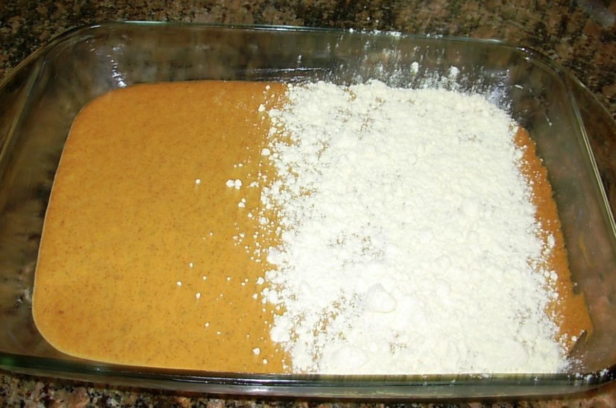 The cake mix has been partially poured over the pumpkin mixture.